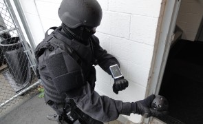 A police officer prepares to throw the Explorer into an unseen stairwell. The camera will then immediately send images of the area back to the smartphone on the officer's wrist.